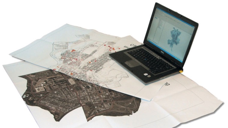 laptop sitting on top of maps