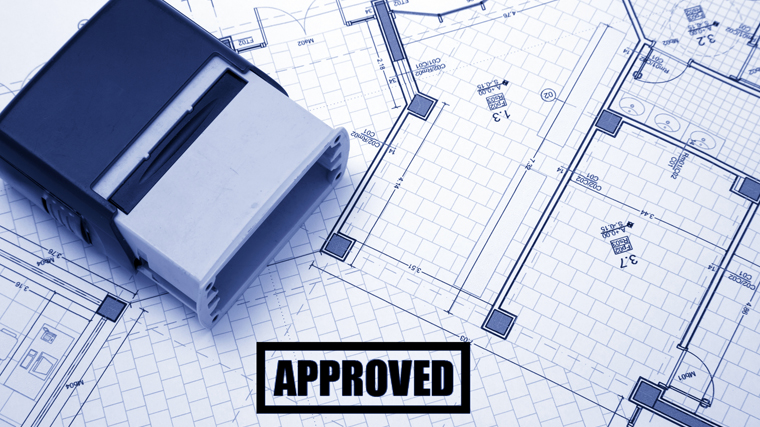 Approved stamp sitting on blueprints